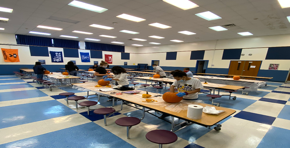 Utica Academy of Science High School students get ready for Halloween by participating in a socially distant pumpkin carving activity.